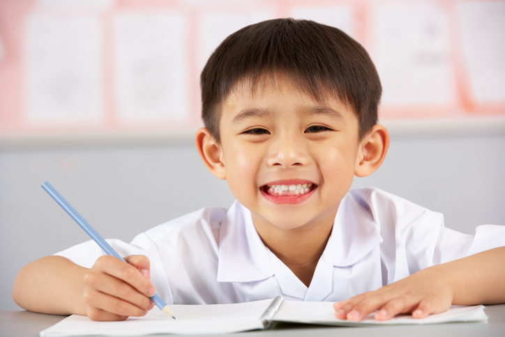 Male Student Working At Desk In Chinese School Classroom Writing In Book Smiling To Camera